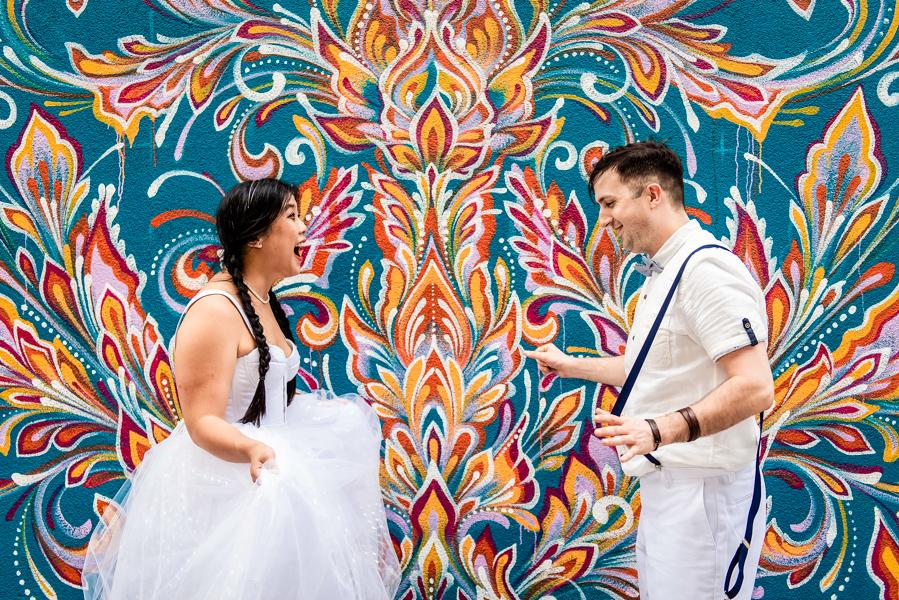 bride and groom posing in front of a Philadelphia mural