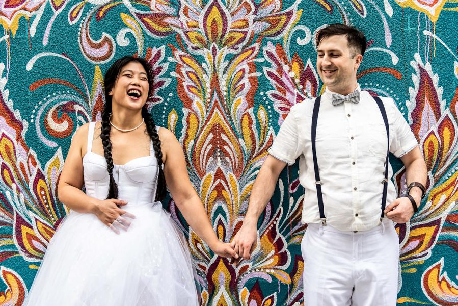 bride and groom posing and smiling in front of a Philadelphia mural