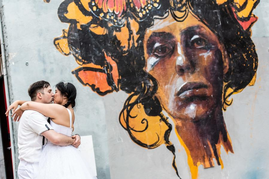 bride and groom kissing in front of a Philadelphia mural