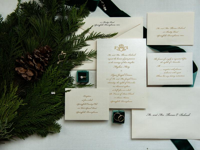 Wedding invitation suite with rings and some of the bride's and groom's accessories