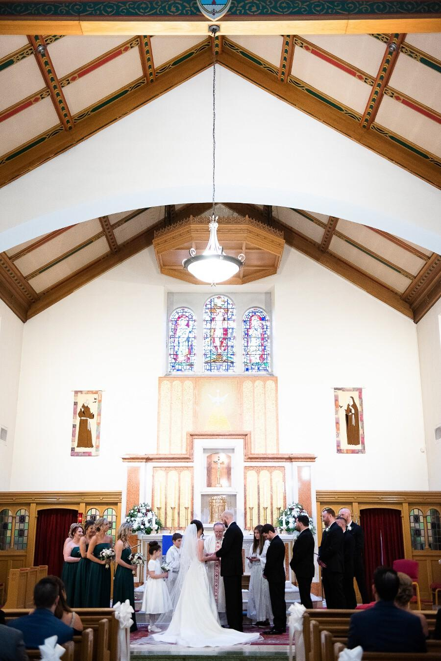 Bride and groom stand on the altar at church with priest and bridal party