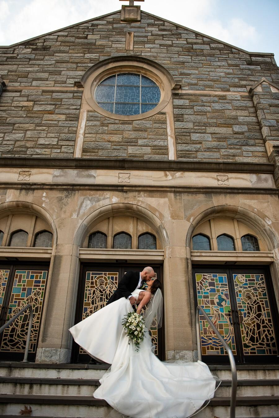 Outside the church, groom dips bride for a photo with veil and gown flowing over the stairs