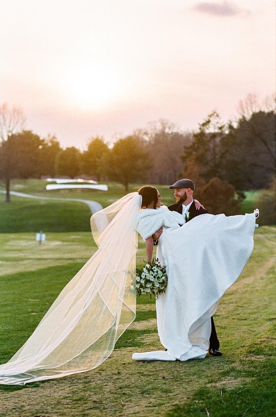 Groom picks up bride for outdoor photo, with bride's veil flowing behind her