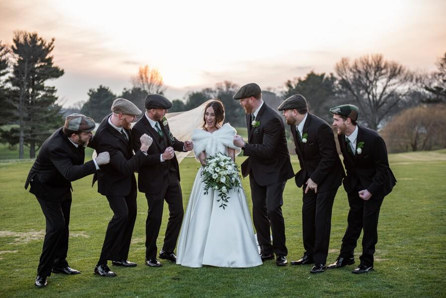 Bride poses with groomsmen on her wedding day