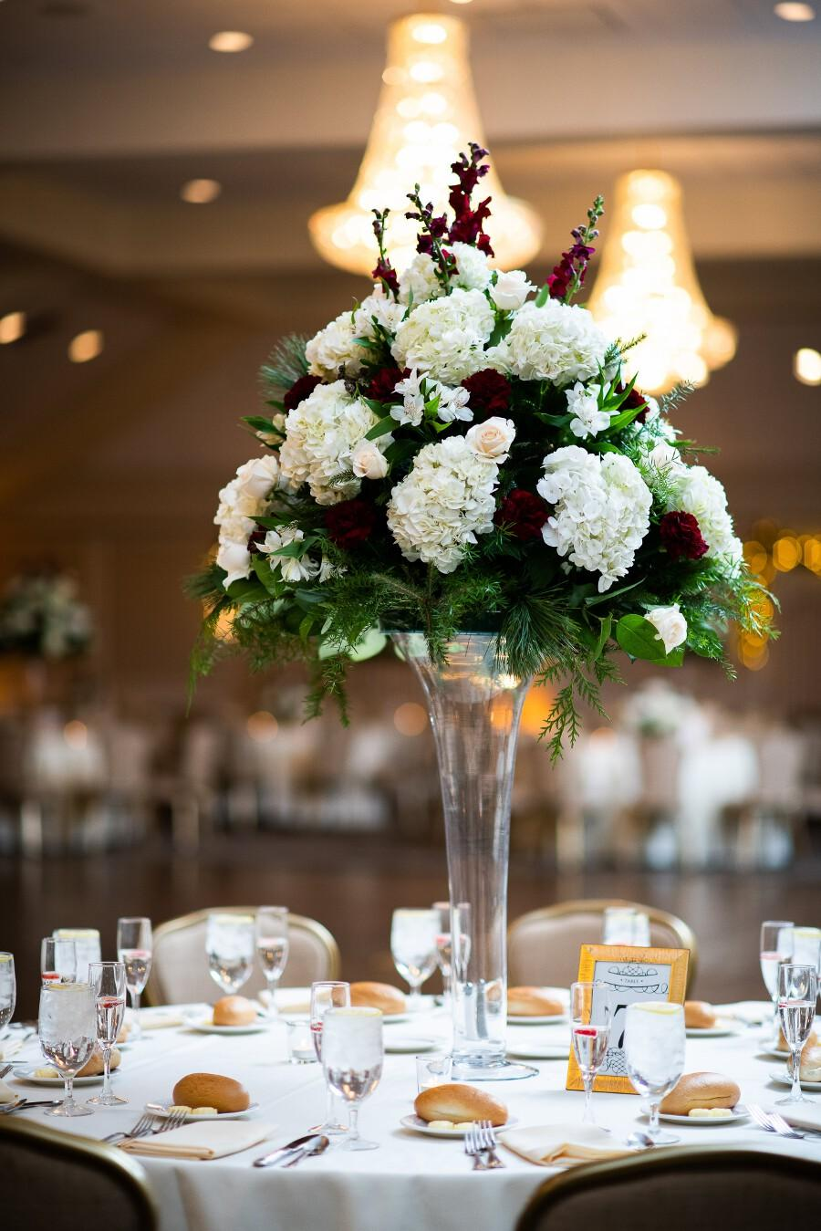 Tall floral arrangement with white, burgundy, and pale pink flowers and greenery