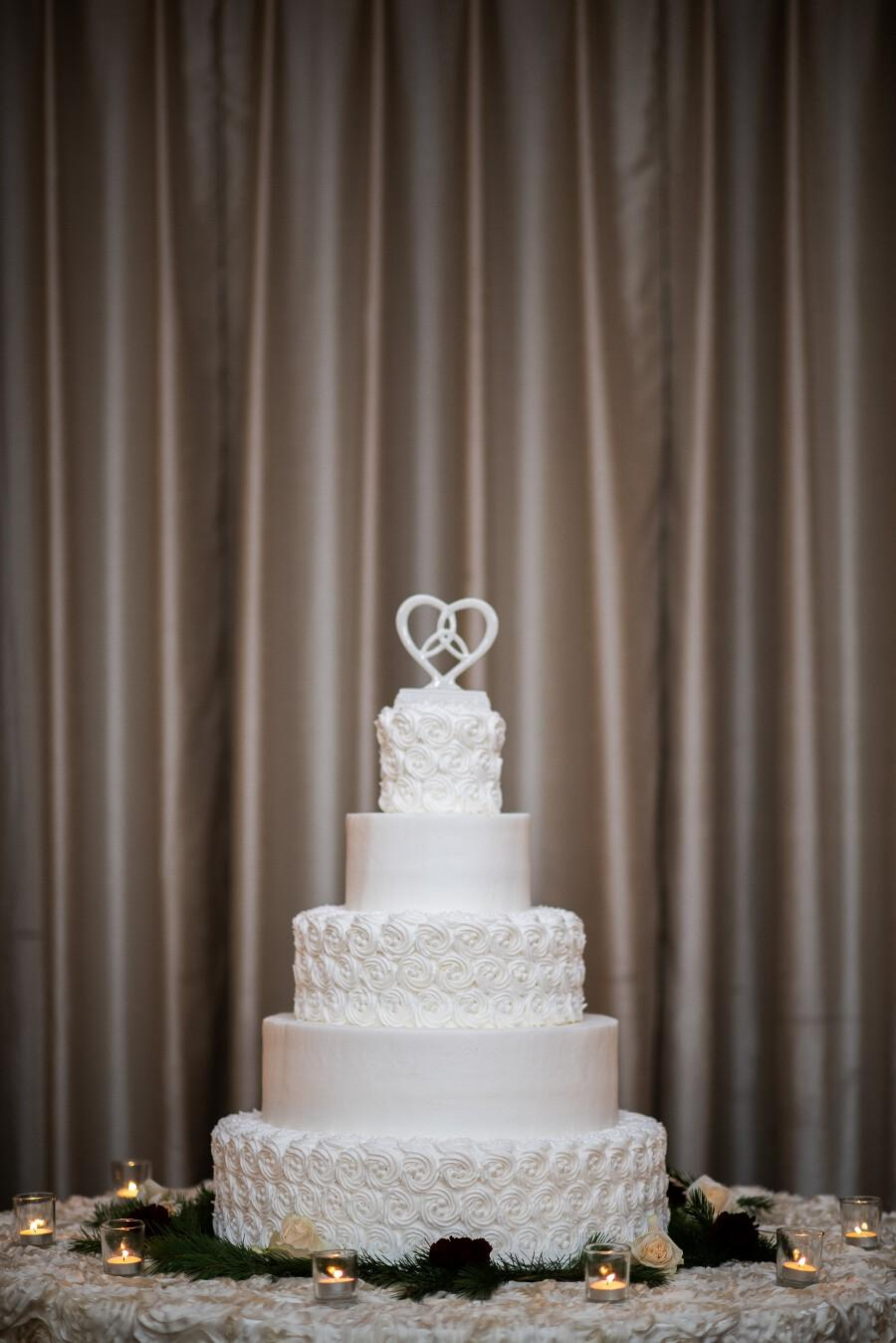 Beautiful white wedding cake with heart cake topper
