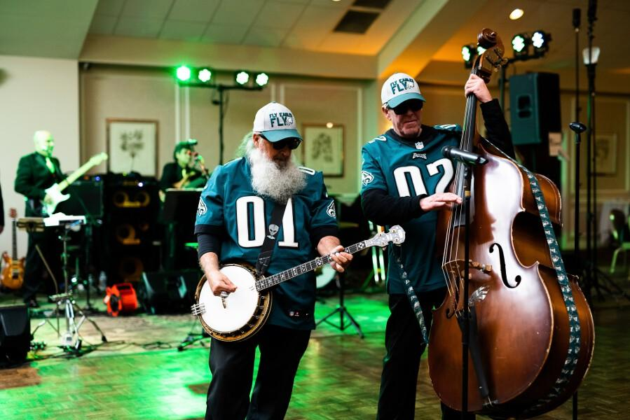 Band playing banjo and cello, wearing Philadelphia Eagles jerseys and hats