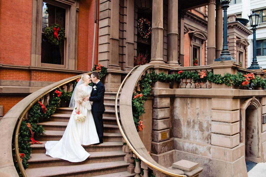 Bride and groom posing on outside steps of The Union League in Philadelphia, PA