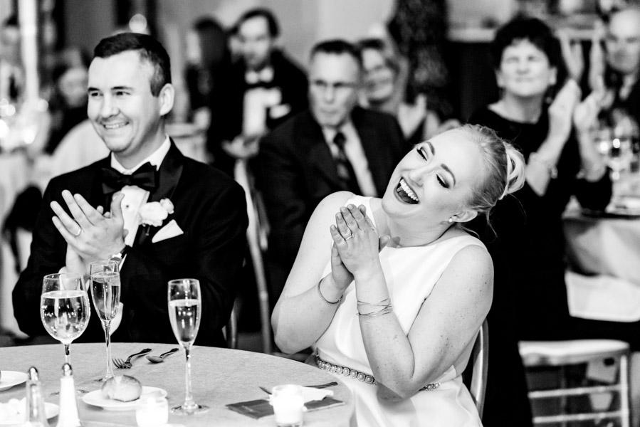 Bride and groom clapping and smiling during wedding reception