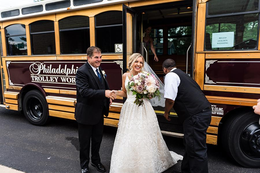 bride and father arrive for wedding in trolley with conductor by ashley gerrity photography and philly in love