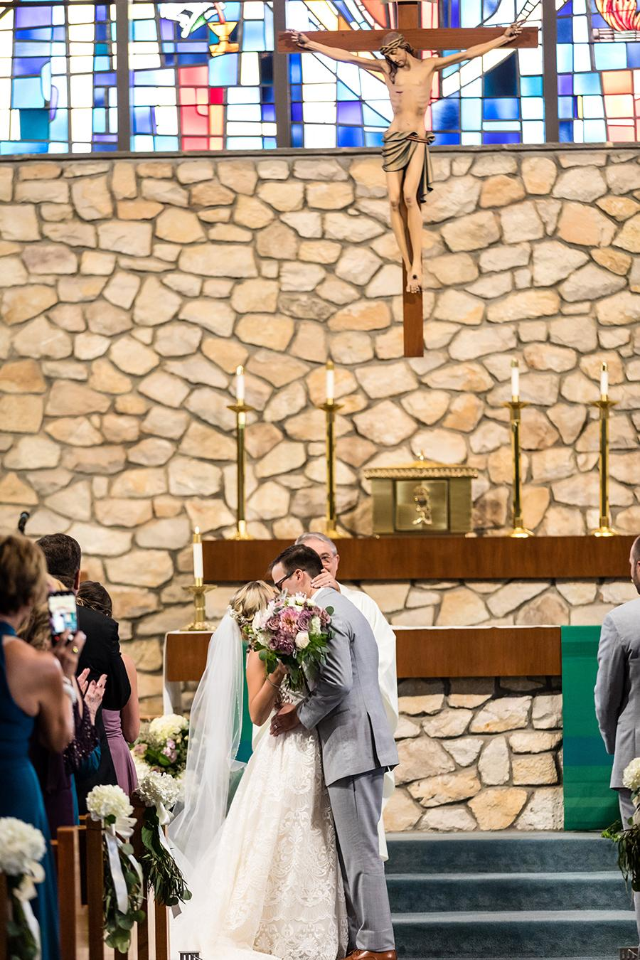 bride and groom kissing in church wedding by ashley gerrity photography and philly in love