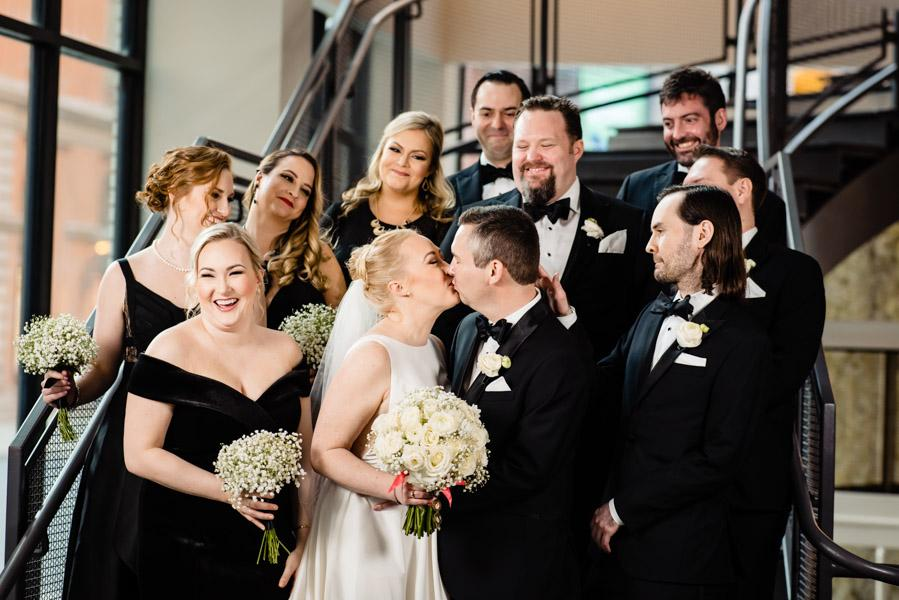 Bride and groom kiss as bridal party smiles