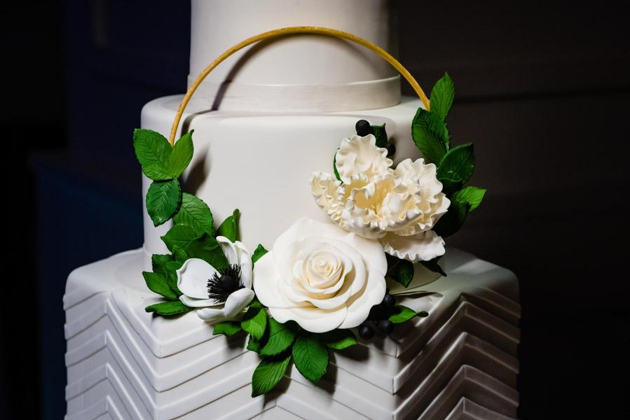 Close-up of sugar leaves and flowers on wedding cake