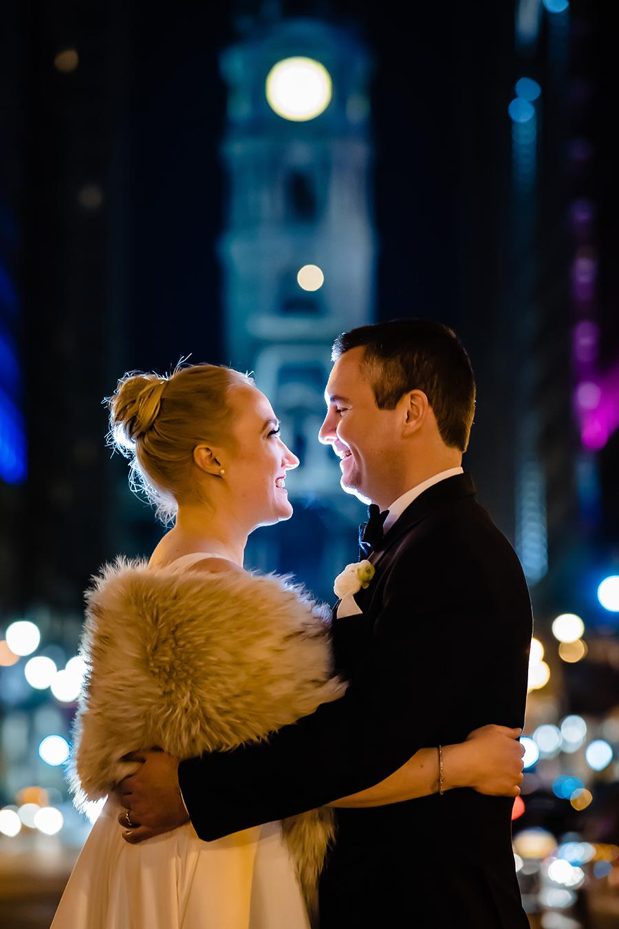Bride and groom pose facing each other with Philadelphia's City Hall in the background, at night