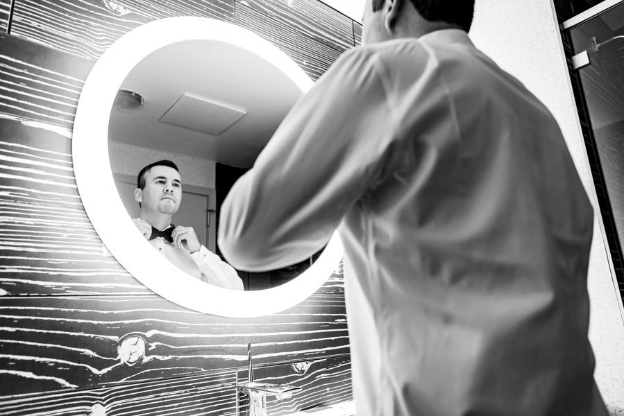 Groom looking in mirror tying bowtie for wedding day