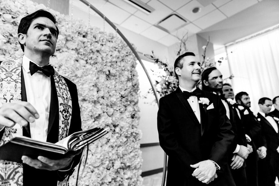 Wedding officiant, groom, and groomsmen wait for the bride to walk down the aisle