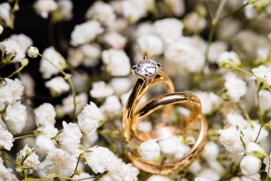 Wedding bands and an engagement ring photographed in flowers