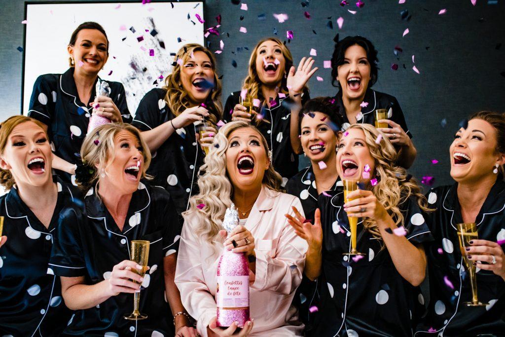 bride and bridesmaids pop confetti champagne