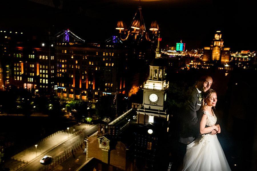 married couple embrace near philadelphia skyline by daniel moyer photography