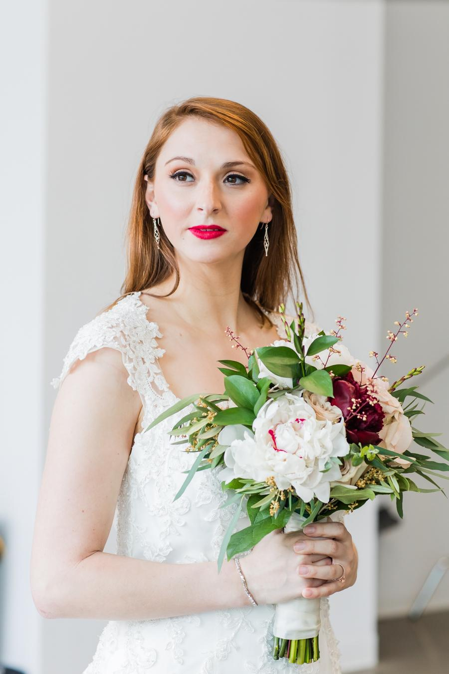 bride to be wearing red lips and lace wedding dress with makeup by Dolly Marshall
