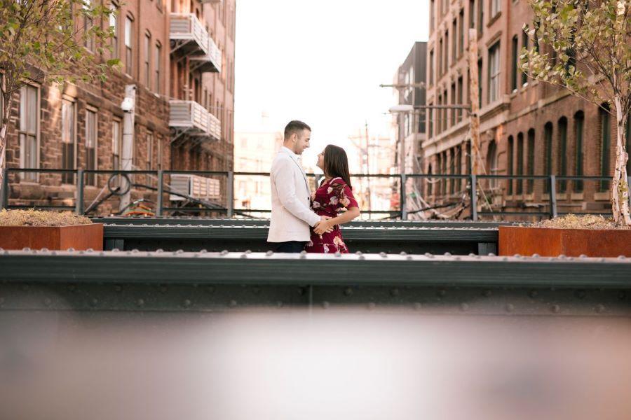 engaged couple embrace outside