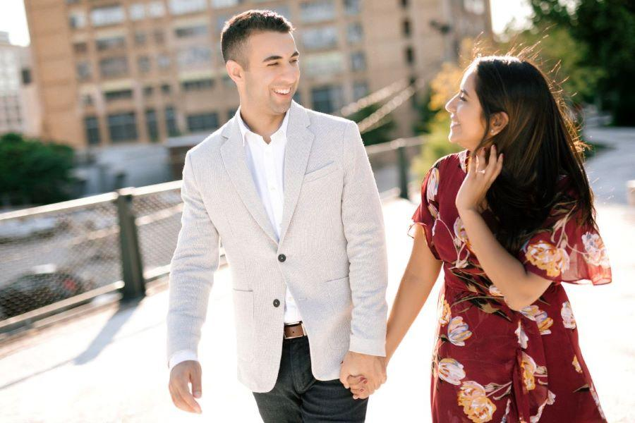 couple holding hands at rail park