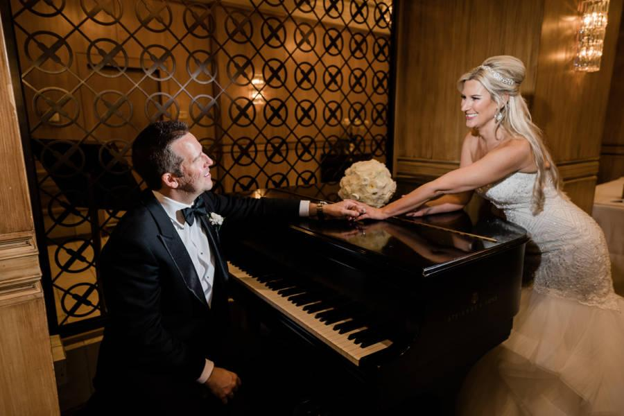 bride and groom pose with baby grand piano