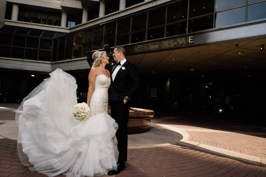 bride and groom stand outside of hotel