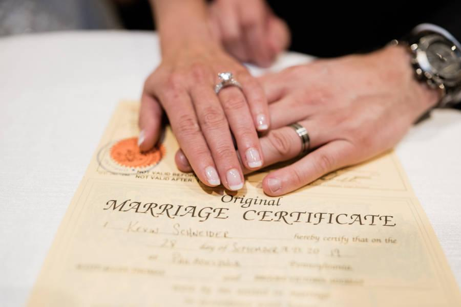 bride and groom's hands on marriage certificate by j & j photography studios