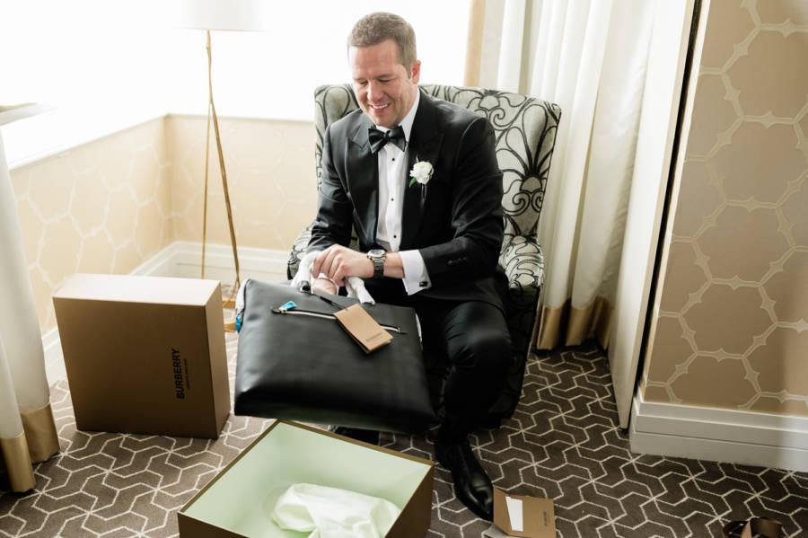groom receiving briefcase by j & j photography studios