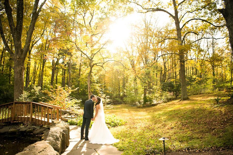 bride and groom kiss by bridge
