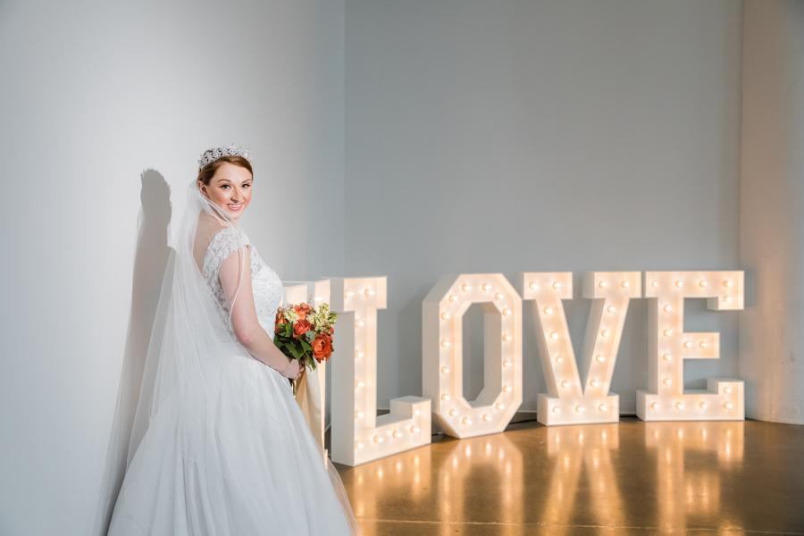 bride wearing tiara and makeup by Dolly Marshall in front of love sign