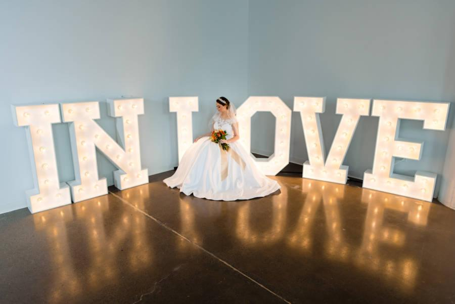 bride wearing ballgown and tiara in front of love sign by slays displays
