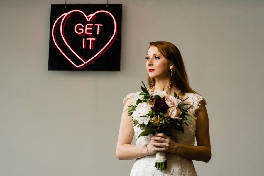 bride wearing lace wedding dress and holding bouquet in front of neon sign