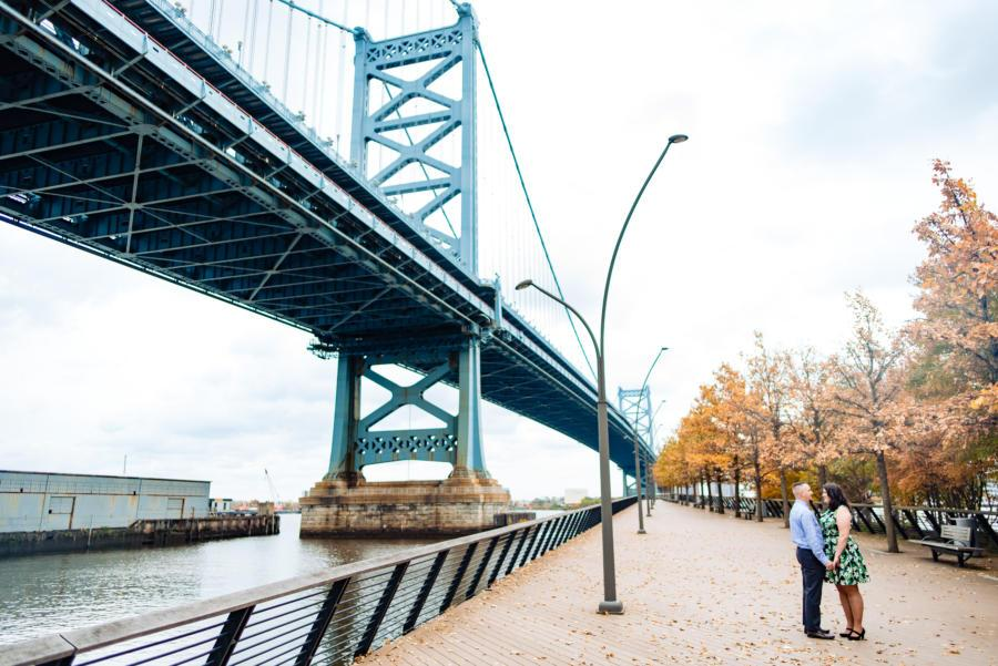 couple holding hands by bridge