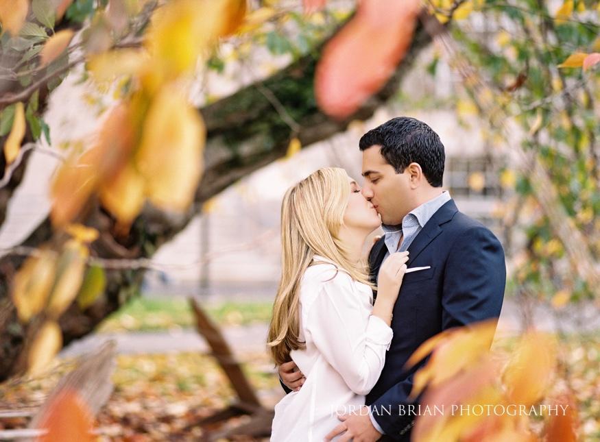 couple kissing among Autumn leaves