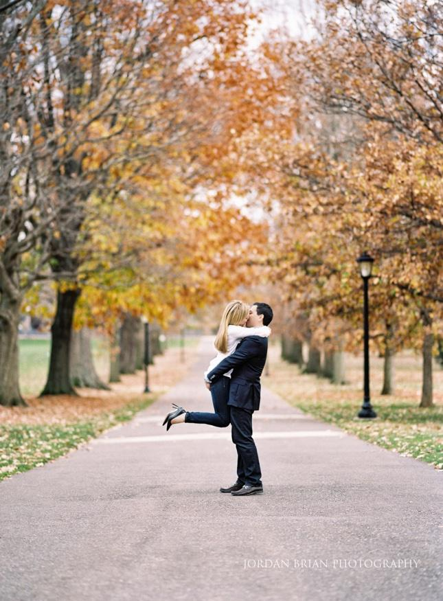 man lifting lady into air on walkway