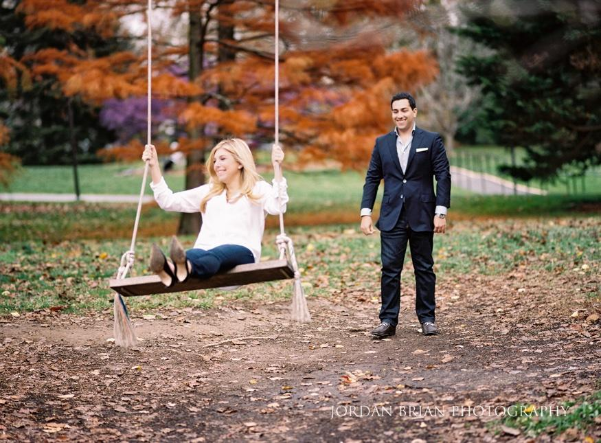 man pushing lady on swing on college campus