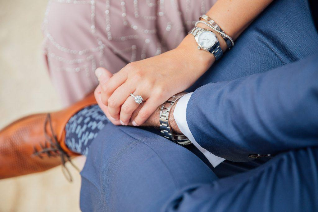 woman and man holding hands showing engagement ring