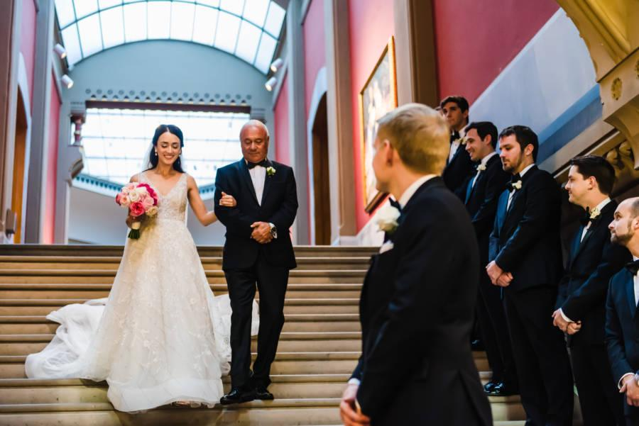 bride walking down stairs with father