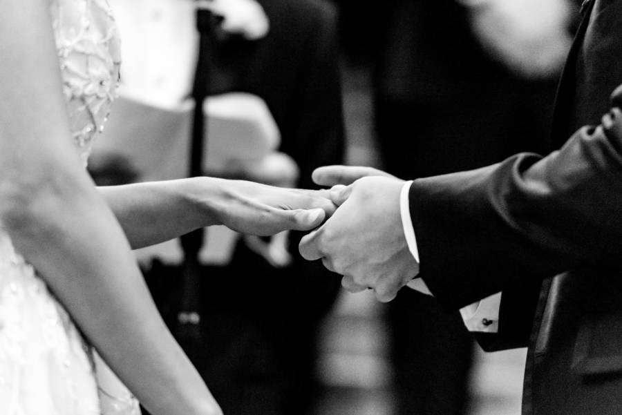 groom placing ring on brides finger at wedding