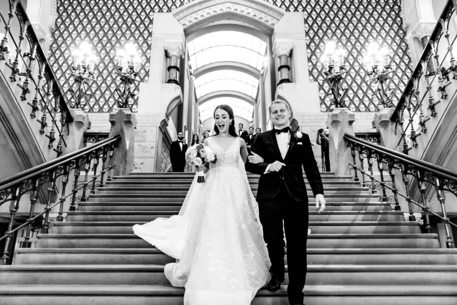 bride and groom walking down stairs at wedding