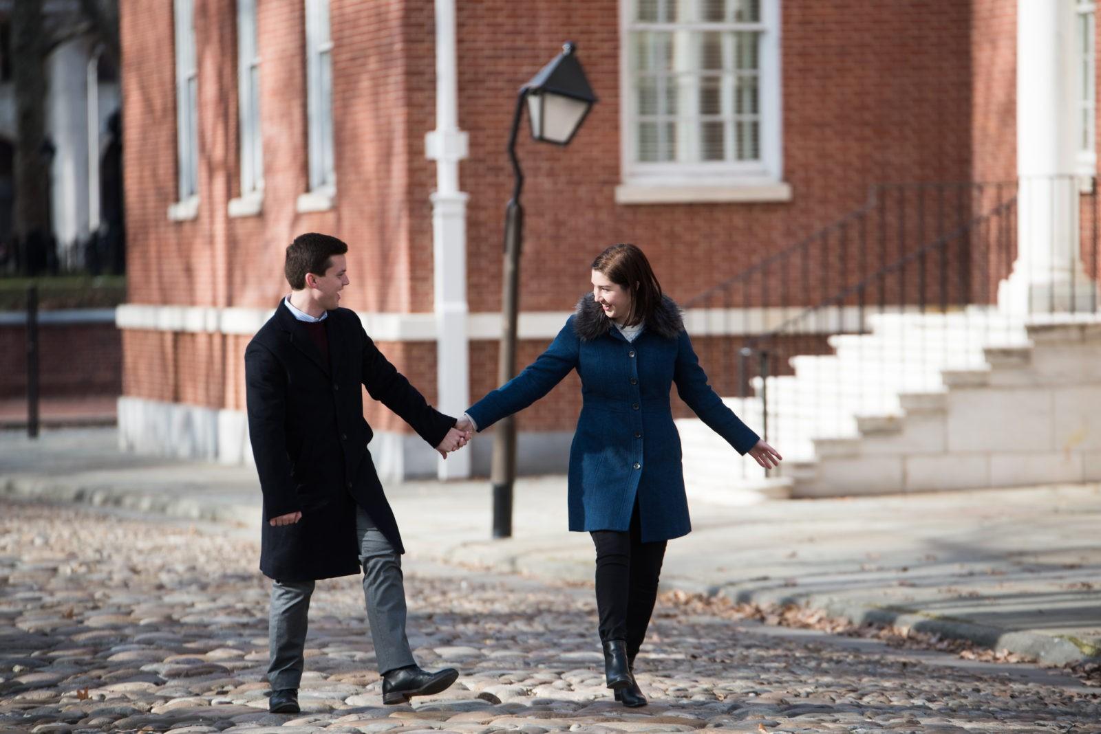 couple holding hands on cobblestone street