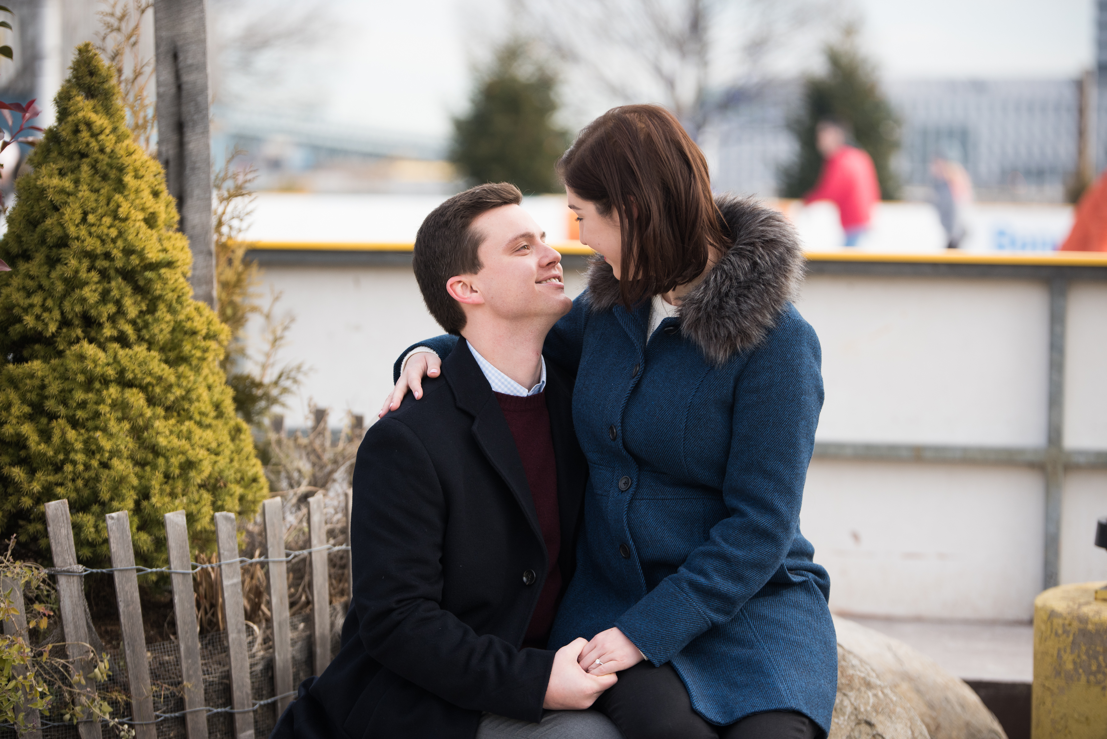 engaged couple sitting on bench outside