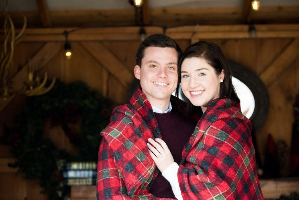 couple under plaid blanket in cabin
