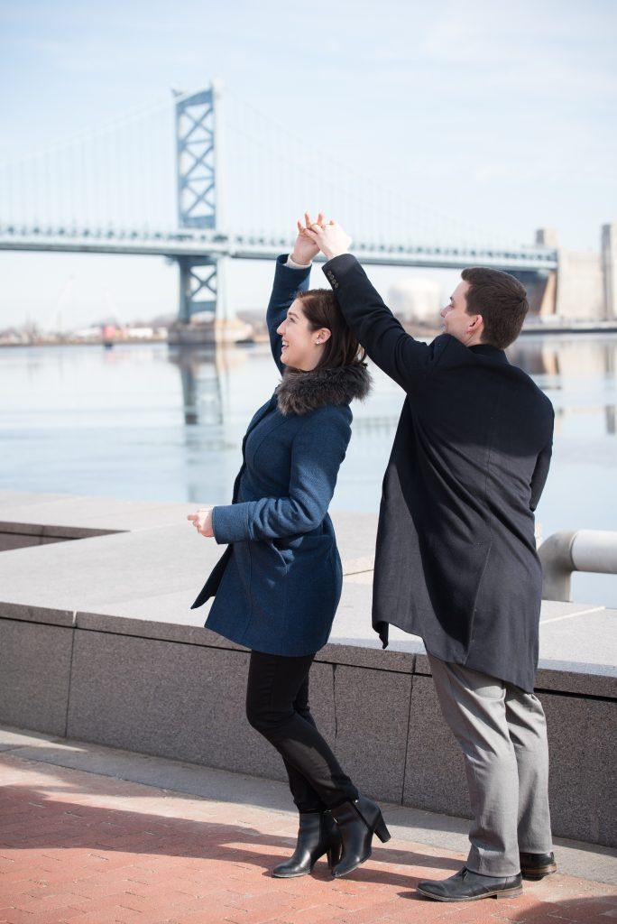 man spinning woman while dancing near bridge