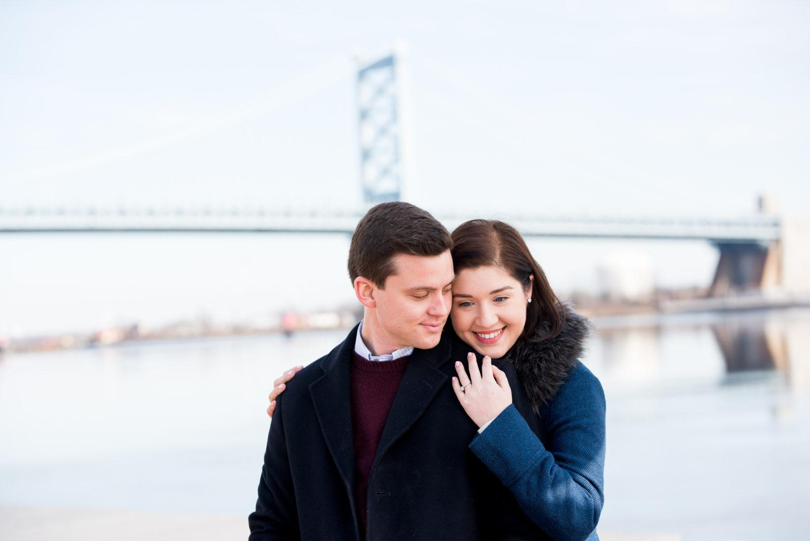 couple embracing outside in front of bridge