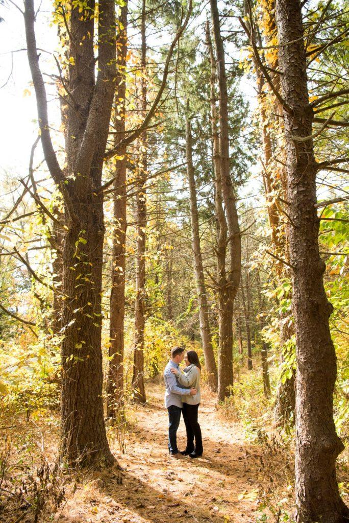 couple embracing among tall trees