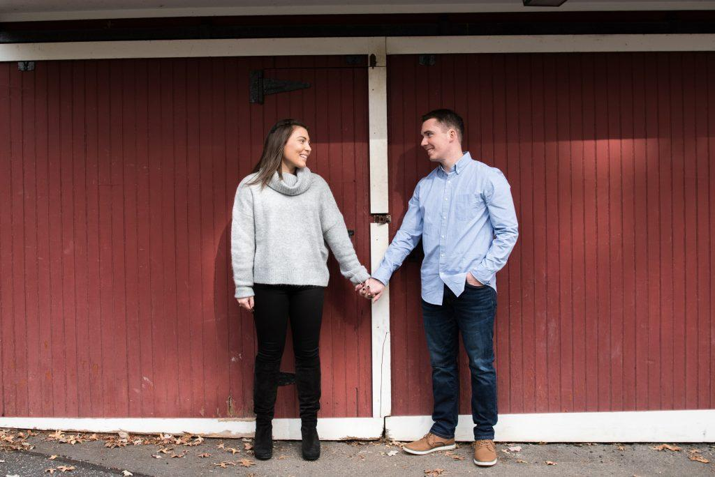 couple holding hands in front of red barn