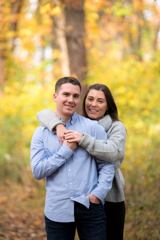 couple embracing in Autumn leaves